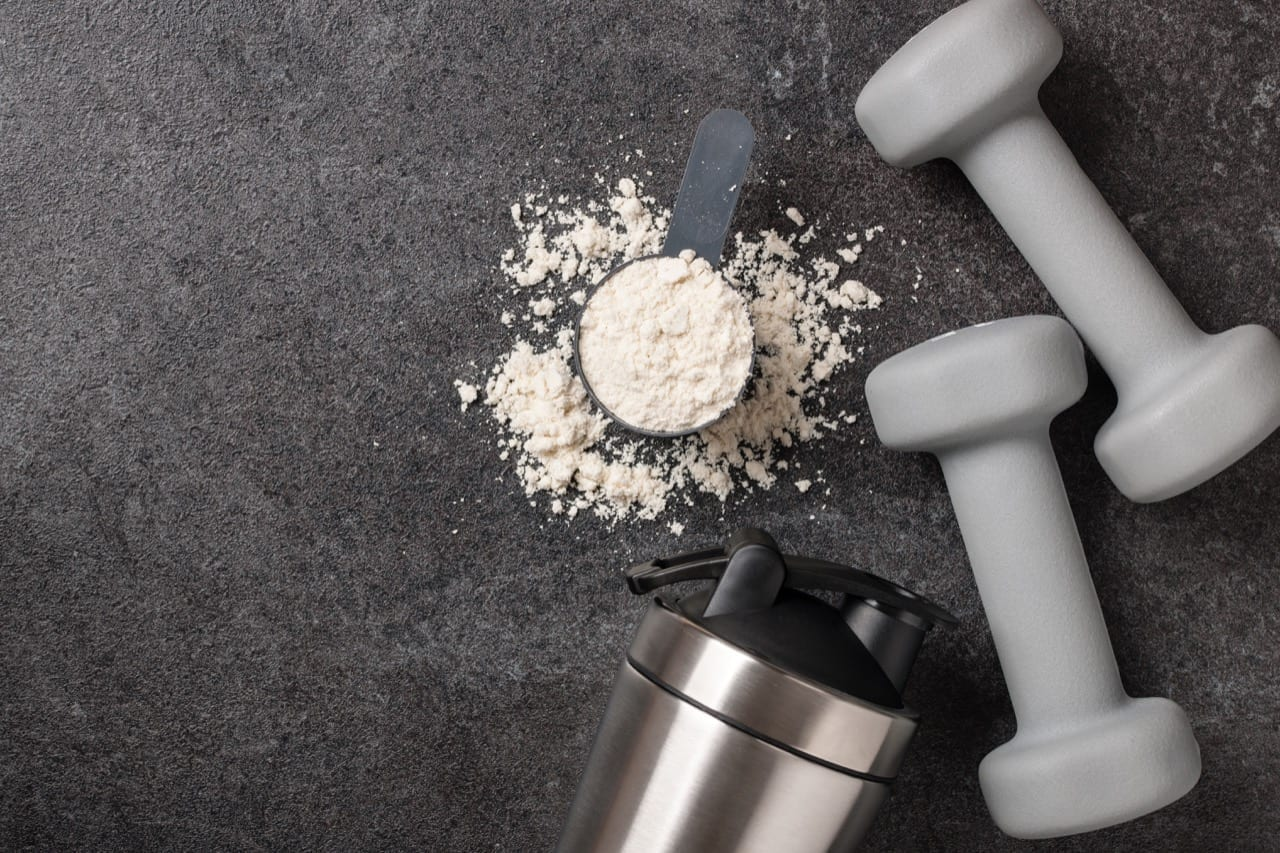 Whey protein powder, shaker and dumbbells on black