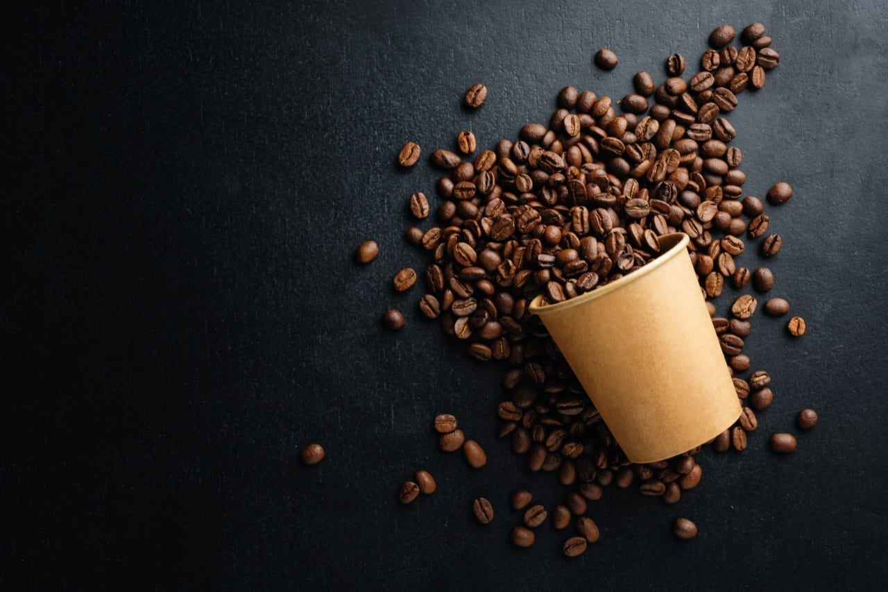 Coffee or zero waste concept. Coffee beans in paper cup on dark background.