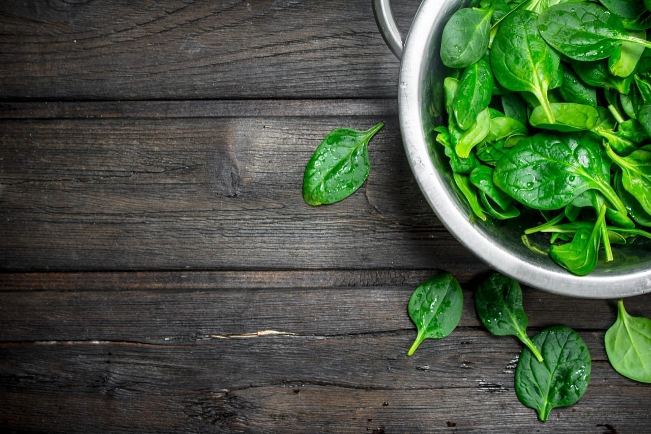 Spinach in a saucepan. On wooden background