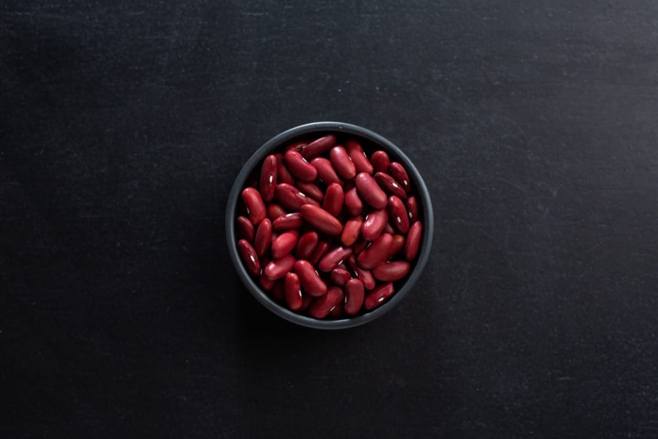 Mockup of red beans in small bowl on dark background.