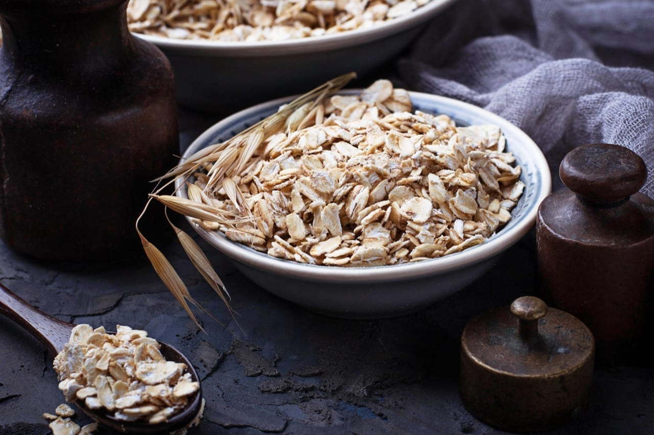 Oat flakes in bowl and spikelets. Selective focus