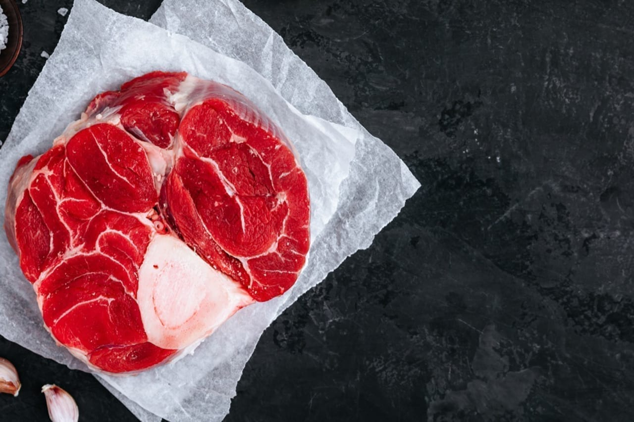 Raw Osso Buco Meat with seasonings on dark stone background. Top view with copy space.