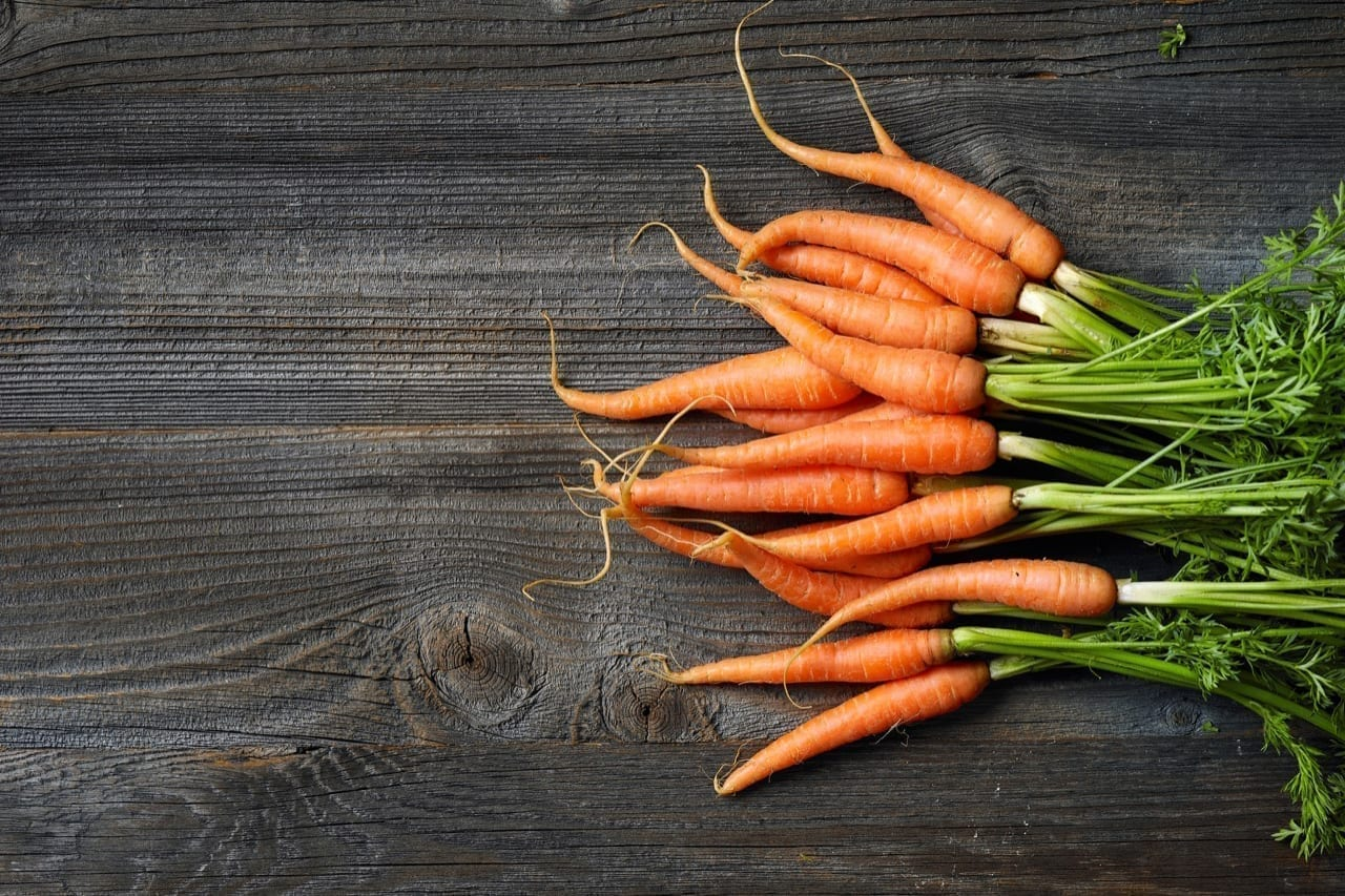 fresh raw carrots on rustic kitchen table, top view