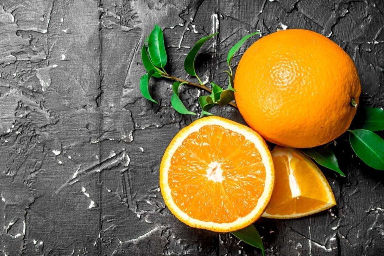 Fresh ripe oranges with leaves. On black rustic background
