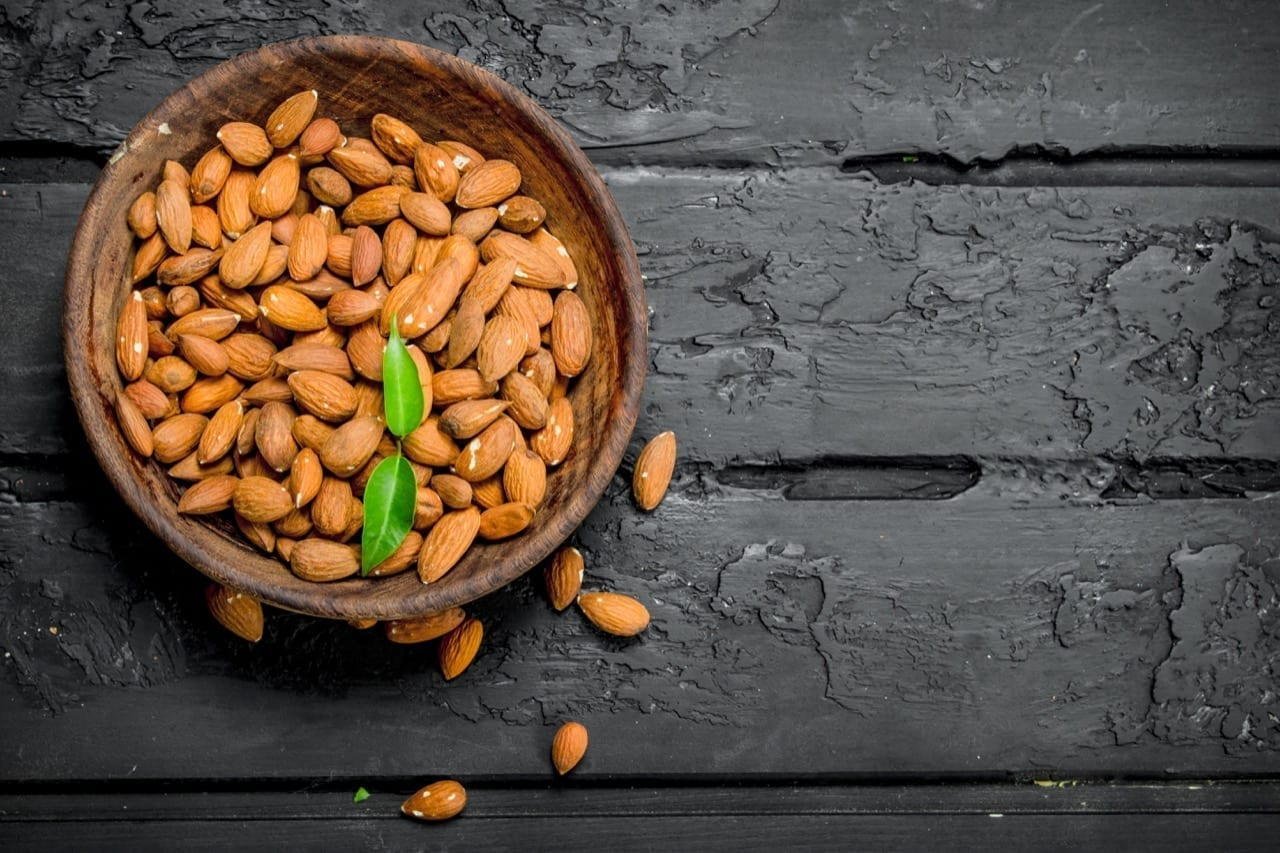 Almonds in bowl. On black rustic background.