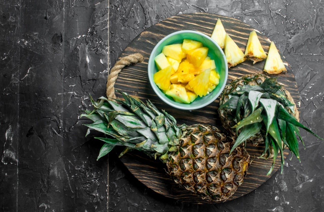 Slices of pineapple in a bowl and whole fresh pineapples on a tray. On black rustic background