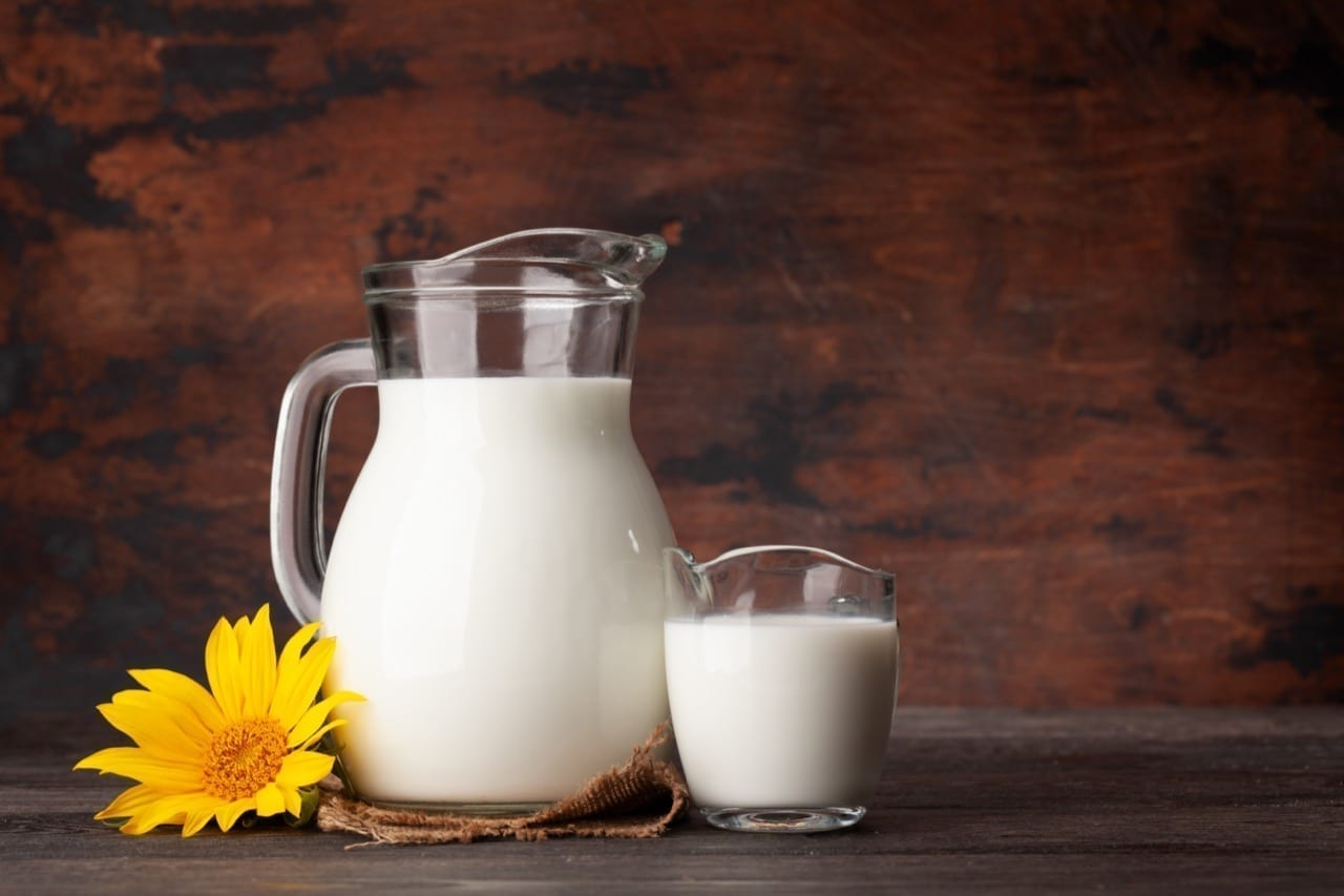 Milk in glass jug. In front of wooden background. With copy space
